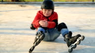 Injured young boy falling off skate, sitting on the floor video