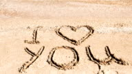 Inscription I love you on sand. video