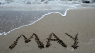 Inscription of the name of month on sand, the beach. video