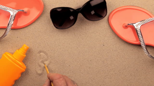 RELAX inscription written by hand on the sand, among beach accessories video