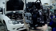 Inside the service autofocus engine hangs in front of a white car video