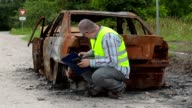 Inspector checking and writing near burned down car wreck on the side of the road video