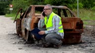 Inspector talking on smart phone near burned down car wreck on the side of the  road video