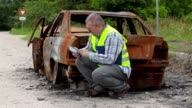 Inspector using tablet PC near burned down car wreck on the side of the road video