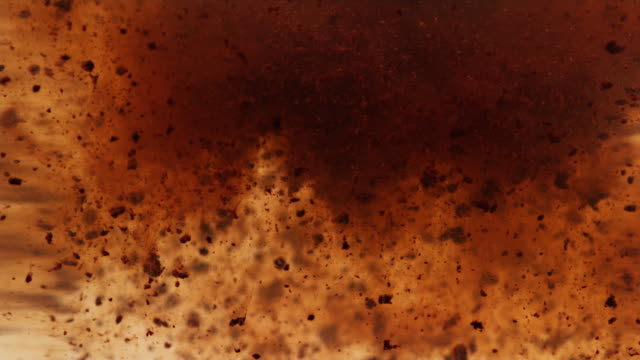 Instant coffee particles dissolving in water, slow motion video