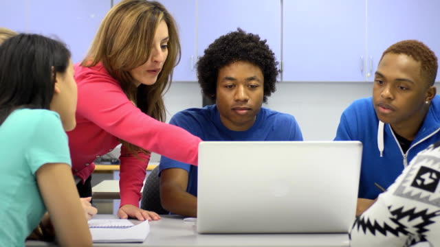 Instructor Assists Students with Laptop Computer video