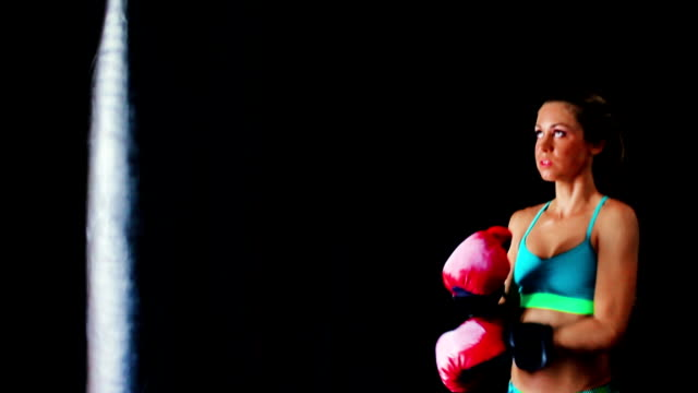 Intense Female Athlete Exercising for Self Defense with Red Boxing Gloves and Black Body Bag. video