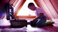 Intensively purple-toned footage: a little boy withdrawing toys from a chest in his attic room video