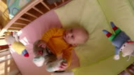 interested baby boy look at carousel toy spin over bed. video