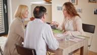 Interior designer explaining her design ideas to a senior couple in their home video