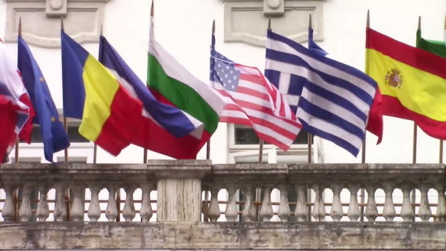 International flags of several countries waving in the wind on the balcony of a building hosting an official meeting video