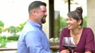 Interracial couple drinking wine on restaurant patio video