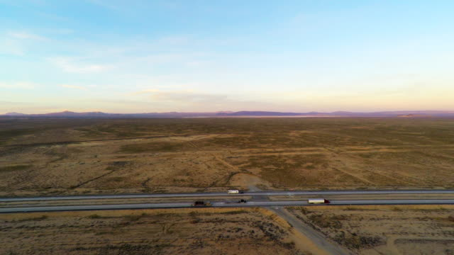 Interstate 40 Mojave Desert traffic trucks driving on highway with barren landscape on each side of freeway 4k aerial birds eye stabilized ultra high definition view video