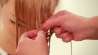 Interweaving of strands of hair. Hairstyle from hair. Close up. White video