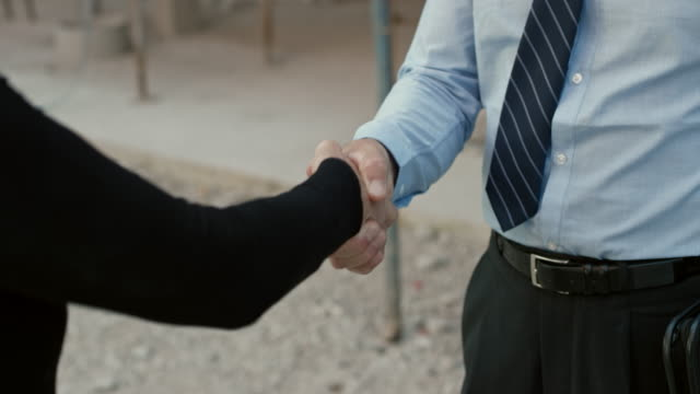 Investor and a female architect shaking hands outside at the construction site video