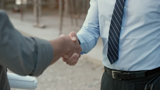 Investor and architect shaking hands outside at the construction site video