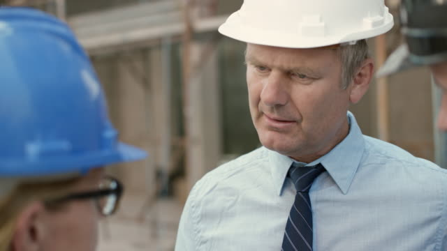 Investor discussing plans with his architects outside at the construction site video