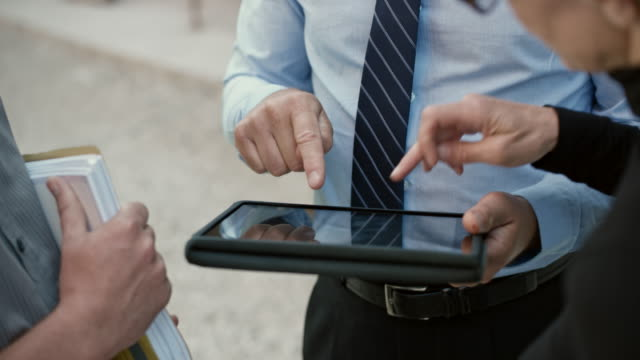 Investor holding a digital tablet and discussing progress of the building with the architect and the engineer video