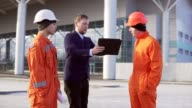 Investor of the project in a black suit examining the building object with construction workers in orange uniform and helmets. They are cheking the drawings using the tablet. video