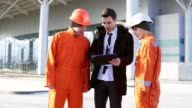 Investor of the project in a black suit examining the building object with construction workers in orange uniform and helmets. They are cheking the drawings using a tablet video