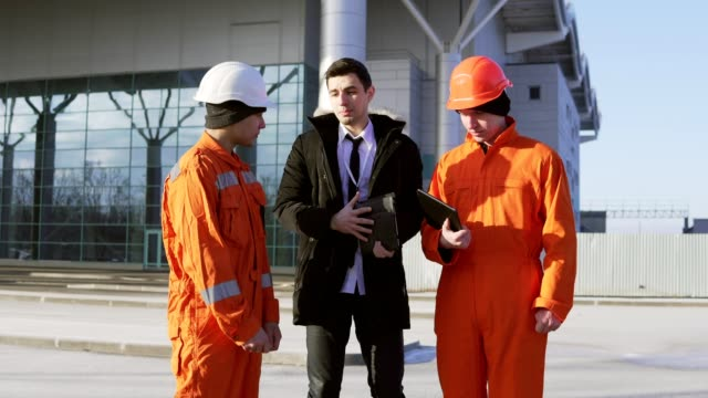 Investor of the project in a black suit examining the building object with construction workers in orange uniform and helmets. video