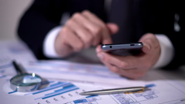 Investor scrolling market newswire on smartphone, examining data for new project video