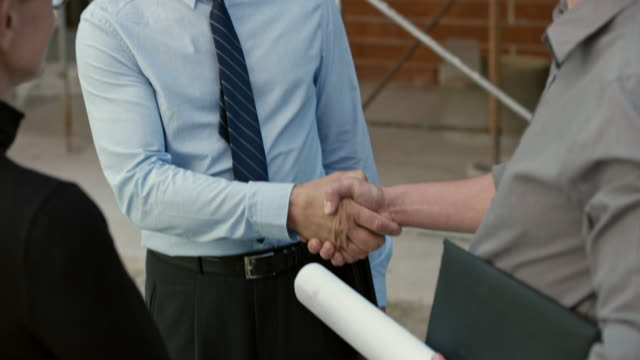 Investor shaking hands with two architects outside at the construction site video