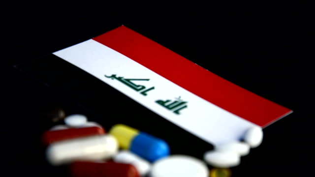 Iraqi flag with lot of medical pills isolated on black background video