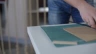 It is close-up image of man cutting paper with stationary knife video