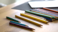 It is close-up image of woman putting colorful pencils on table video
