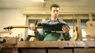 Italian adult man working as craftsman in guitar workshop video