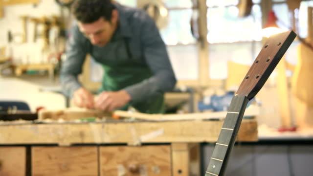 Italian man working as artisan in guitar workshop video