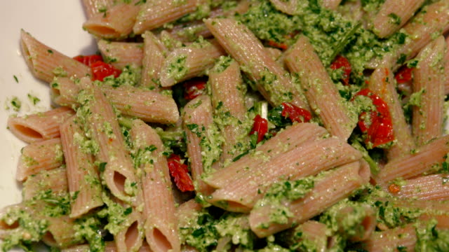 Italian penne pasta dish with pesto and tomatoes rotating close-up video