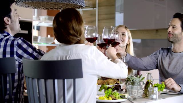 Italian people making toast together with red wine. Four happy real candid friends enjoy having lunch or dinner together at home or restaurant. 4k video video