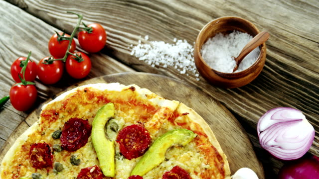 Italian pizza on wooden table with vegetables and spices video