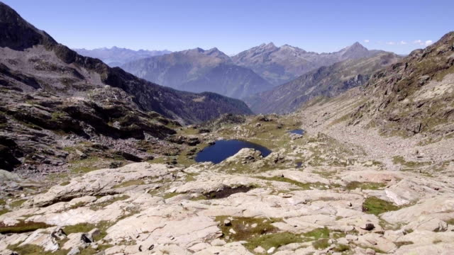 Italy Alps mountains aerial above blue lake reveal in summer sunny day. 4k drone forward flight wide establishing shot video