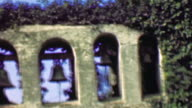 1958: Ivy wrapped ancient church walls hanging bells toll for none. video