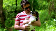 Jack Russell Terrier's puppy in a loving hug of a jolly guy video