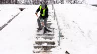 Janitor with snow shovel stepping down and cleaning stairs video