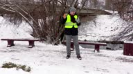 Janitor with snow shovel talking on phone on sidewalk near benches video