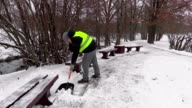 Janitor with snow shovel working near benches video