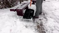 Janitor with snow shovel working  on sidewalk near benches video