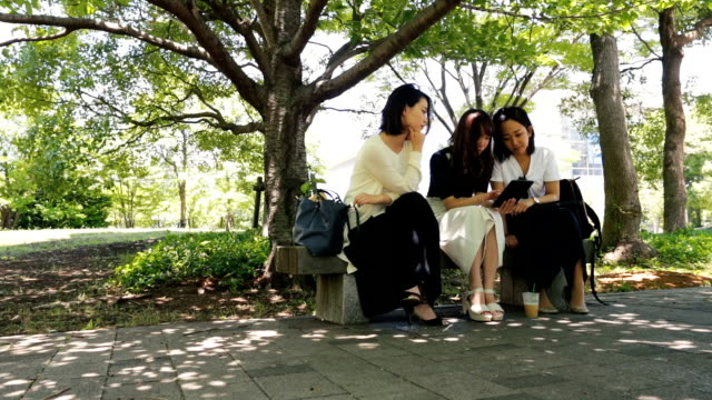 Japanese Business Women Looking at Tablet Computer Outdoors video