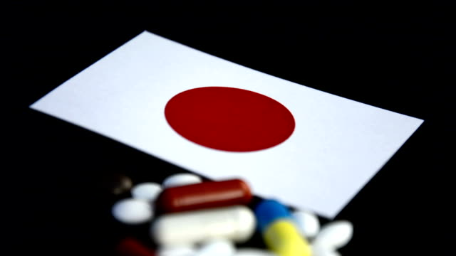 Japanese flag with lot of medical pills isolated on black background video