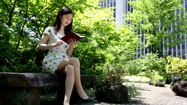 Japanese Woman Reading in a Park in Tokyo video