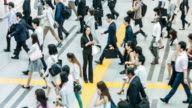 Japanese woman talking on the mobile phone surrounded by commuters video
