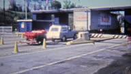 1972: Jeep towing 6-wheel ATV past border crossing. video