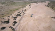 AERIAL: Jeeps driving in a dry riverbed video