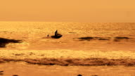 Jet ski rides on the sea waves at sunset. Two men actively spend their vacation at the resort. Human silhouette on the water background video