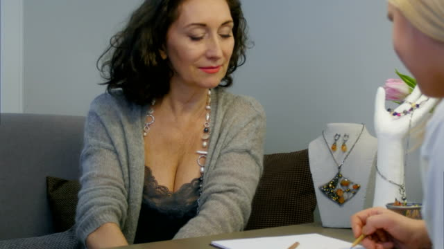 Jewelry designer and elegant woman in studio selecting designs of jewellery video